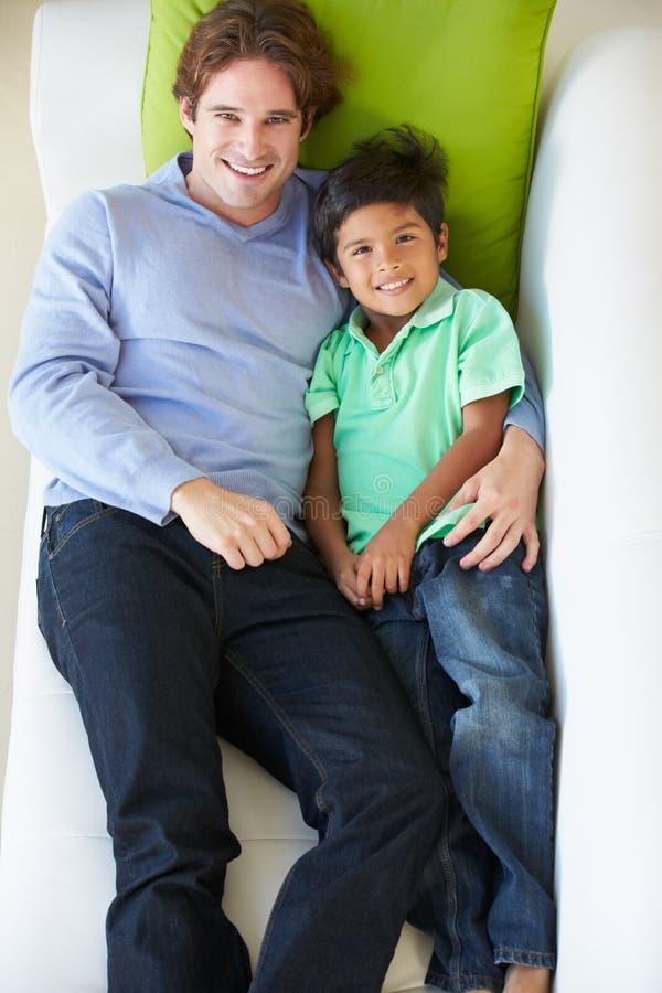 Надземный взгляд отца и сына ослабляя на софе стоковые изображения rf