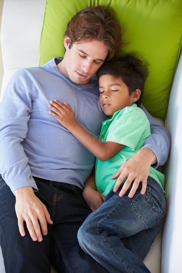 Надземный взгляд отца и сына ослабляя на софе стоковое изображение rf