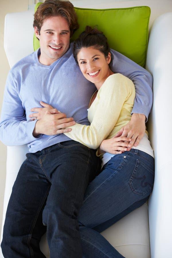Надземный взгляд пар ослабляя на софе стоковые изображения