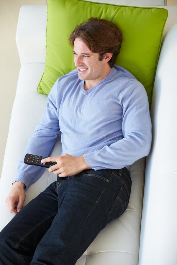 Надземный взгляд человека ослабляя на софе смотря телевидение стоковые фотографии rf