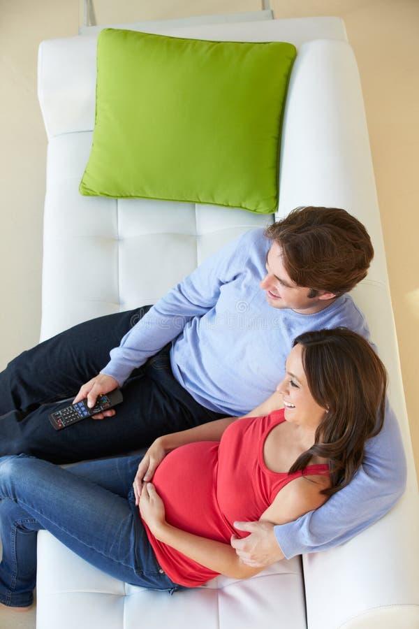 Надземный взгляд человека ослабляя на софе с беременной женой стоковые фото