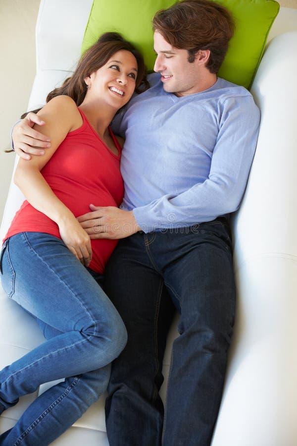 Надземный взгляд человека ослабляя на софе с беременной женой стоковое изображение