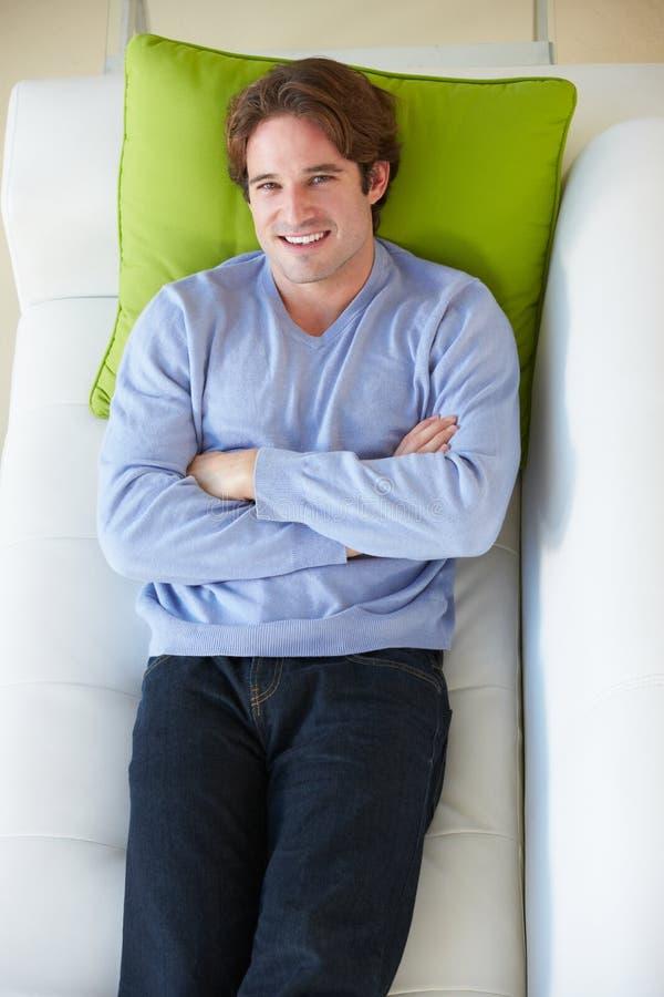 Надземный взгляд человека ослабляя на софе стоковое фото rf