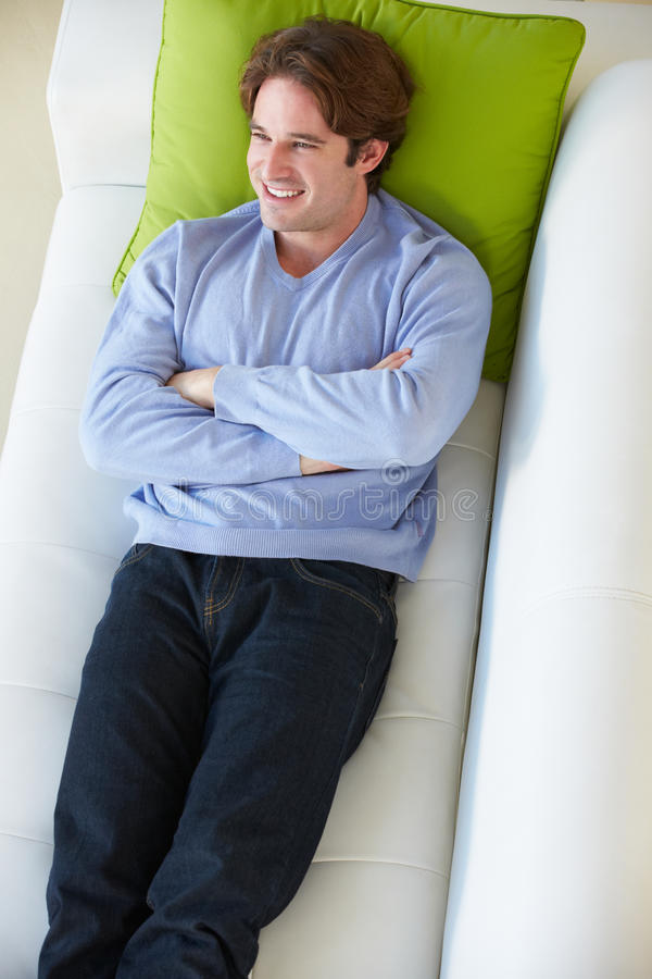 Надземный взгляд человека ослабляя на софе стоковое изображение