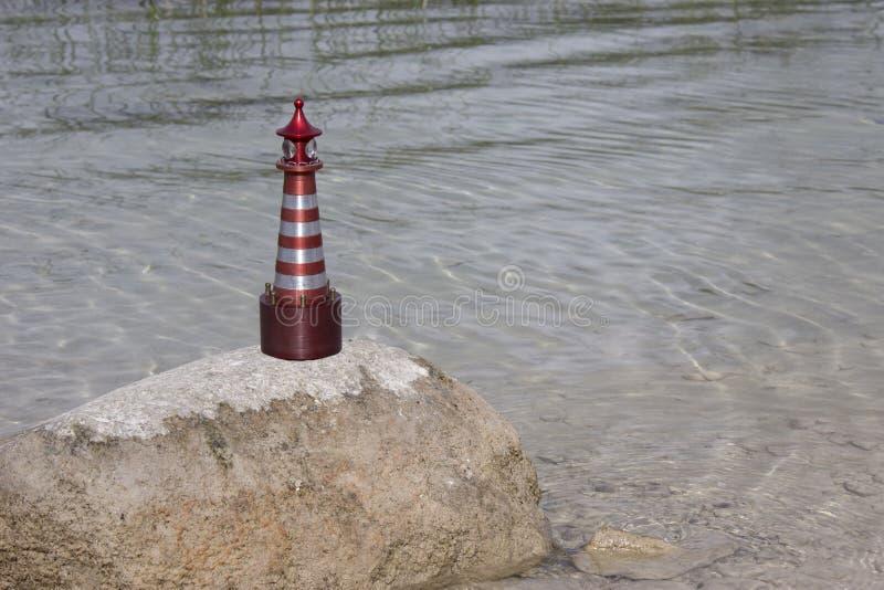 На камне стоит игрушечный маяк, освещенный солнцем стоковые изображения rf