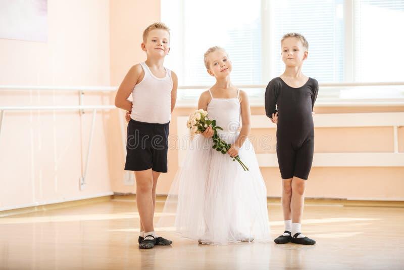 На классе танцев балета: молодые мальчики и девушка с цветками стоковая фотография