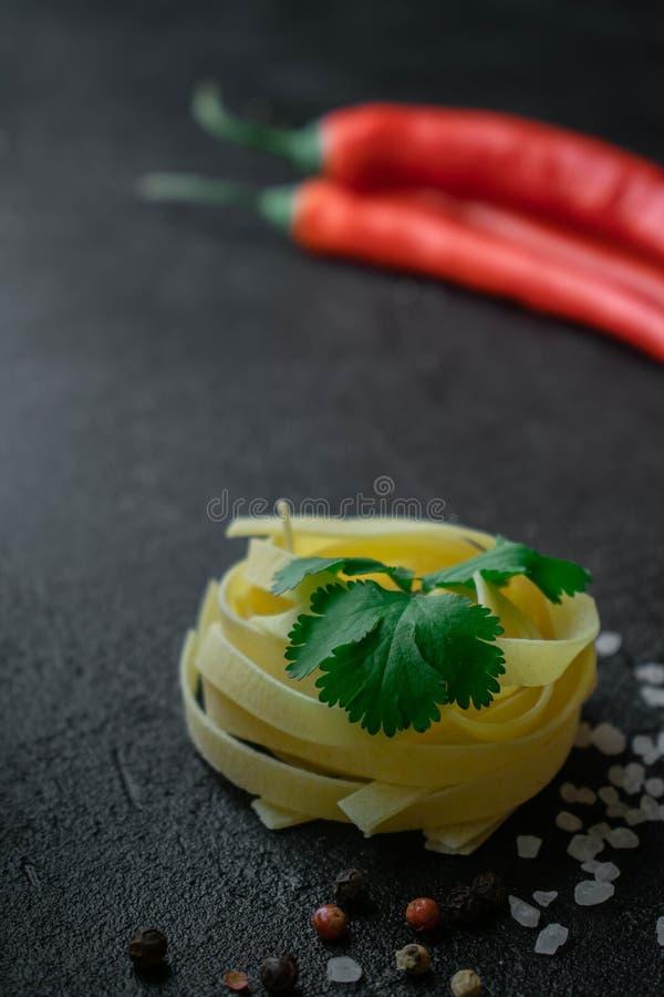 На макаронных изделиях fettuccine темной предпосылки сырцовых с листьями ci стоковые изображения