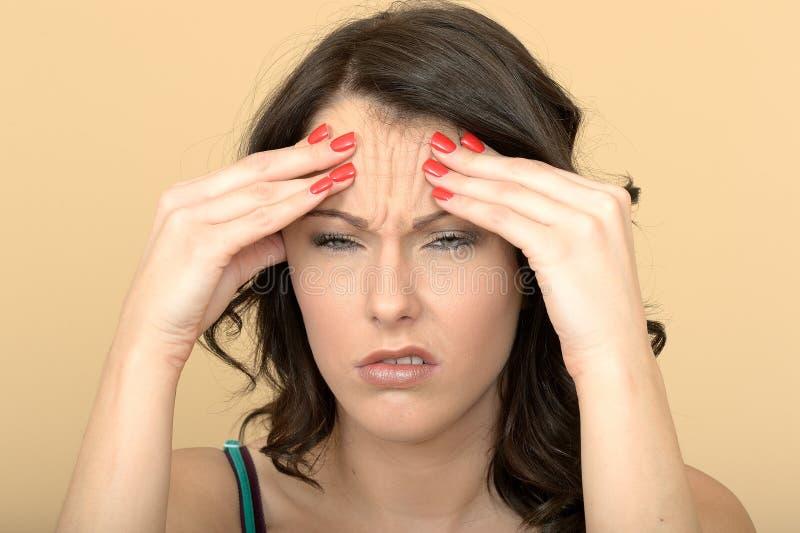 Надоеданная унылая несчастная молодая женщина с тягостной головной болью стоковое изображение