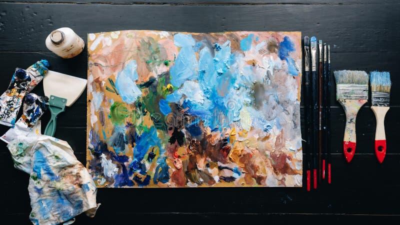 На лож деревянного стола палитра, щетки, краски стоковые фотографии rf