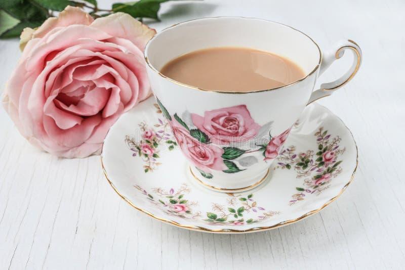 Надоите чай в чашке и поддоннике фарфора, с розовыми розами стоковое фото