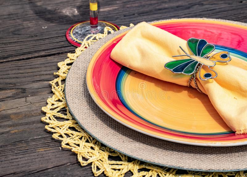 На открытом воздухе обедать патио: Праздничный и красочный tableware в красном, голубом, и лимоне - желтом - вертикаль стоковое изображение rf