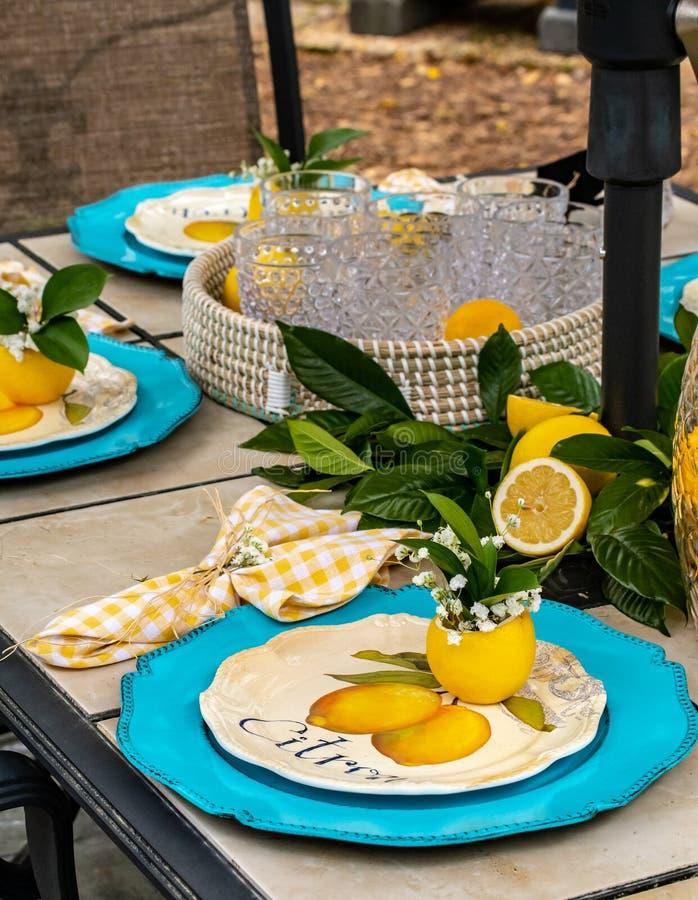 На открытом воздухе обедать патио: Праздничный и красочный tableware в teal и лимоне - желтых - вертикаль стоковые изображения rf