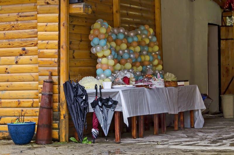 На открытом воздухе партия в парке Rila украшенном с красочными воздушными шарами, тортом и подарками на дождливый день стоковая фотография rf