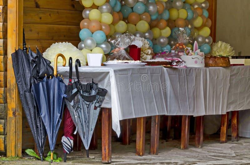 На открытом воздухе партия в парке Rila украшенном с красочными воздушными шарами, тортом и подарками на дождливый день стоковое фото rf