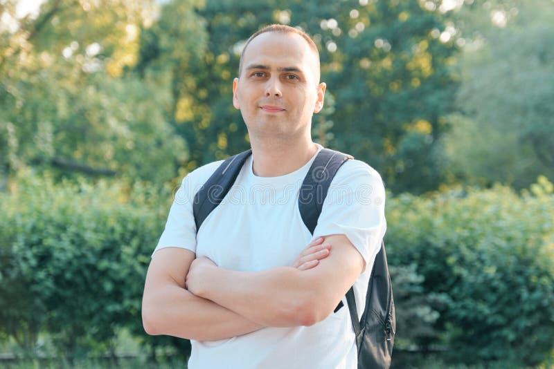 На открытом воздухе портрет зрелого усмехаясь положительного человека Уверенный мужчина в белой футболке с рюкзаком со сложенными стоковая фотография