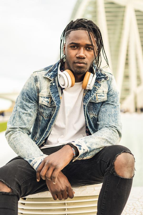 На открытом воздухе портрет красивого и привлекательного молодого африканского человека с наушниками музыки на улице стоковое фото