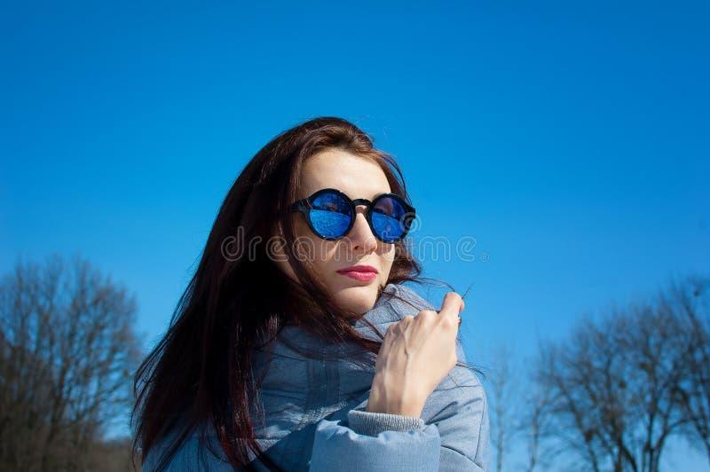 На открытом воздухе портрет маленькой девочки нося отраженные голубые солнечные очки и одежды зимы представляя на ярком небе и об стоковая фотография rf