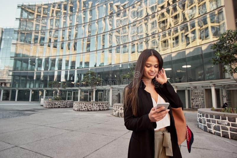 На открытом воздухе портрет молодое красивого используя ее смартфон стоковые фотографии rf