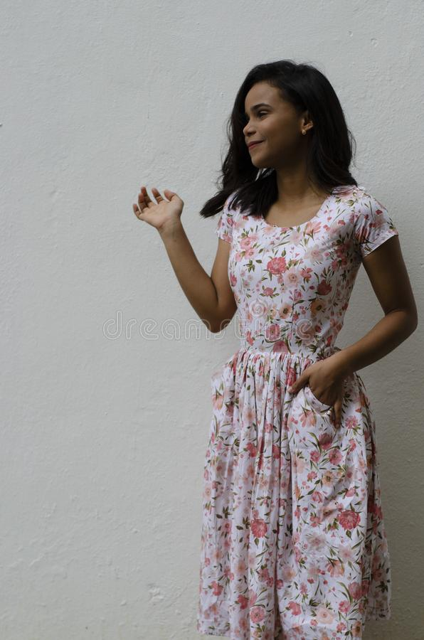 На открытом воздухе портрет молодой красивой девушки 19 до 25 лет Браун-с волосами, стоящ перед белой стеной Носить свежее флорис стоковая фотография rf