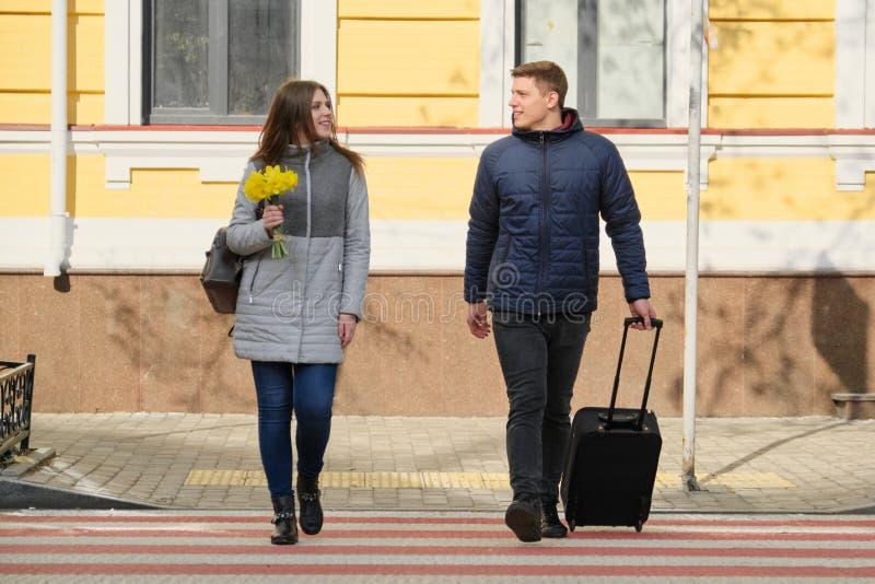На открытом воздухе портрет молодых пар идя с чемоданом на улице города, счастливом молодом человеке и перемещении женщины весной стоковая фотография rf