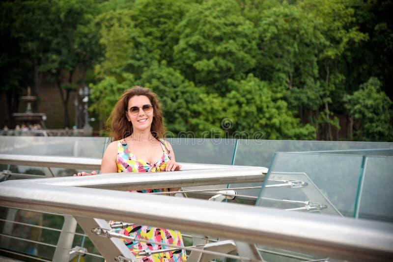 На открытом воздухе портрет образа жизни изумлять блестящую роскошную женщину представляя в центре города Элегантные классические стоковая фотография