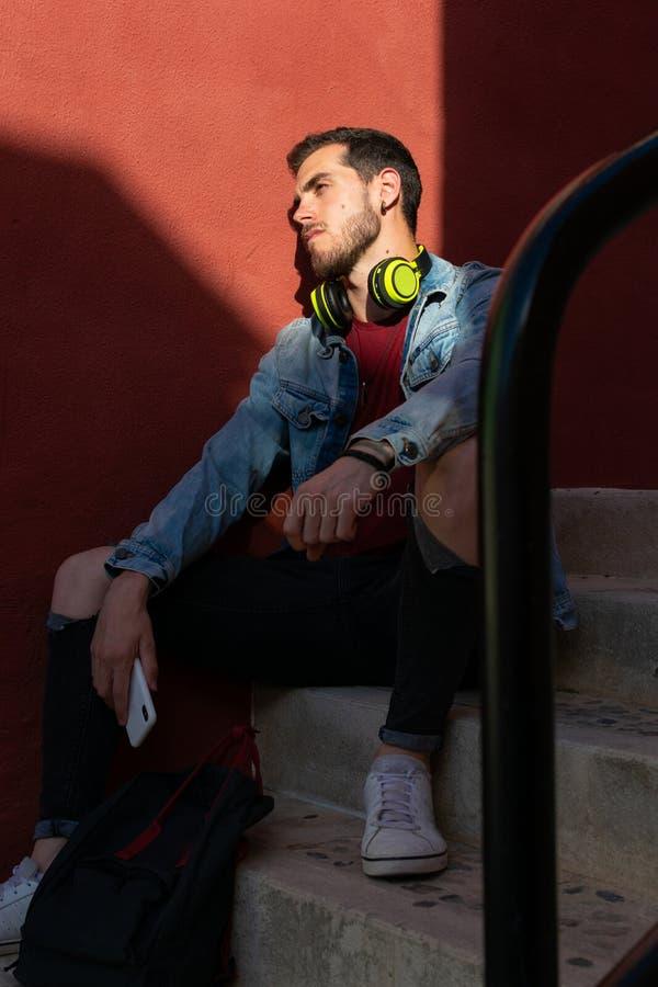 На открытом воздухе портрет современного молодого человека с умным телефоном сидя в улице стоковое изображение