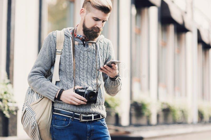 На открытом воздухе портрет современного молодого человека путешественника используя умный телефон на улице стоковая фотография rf