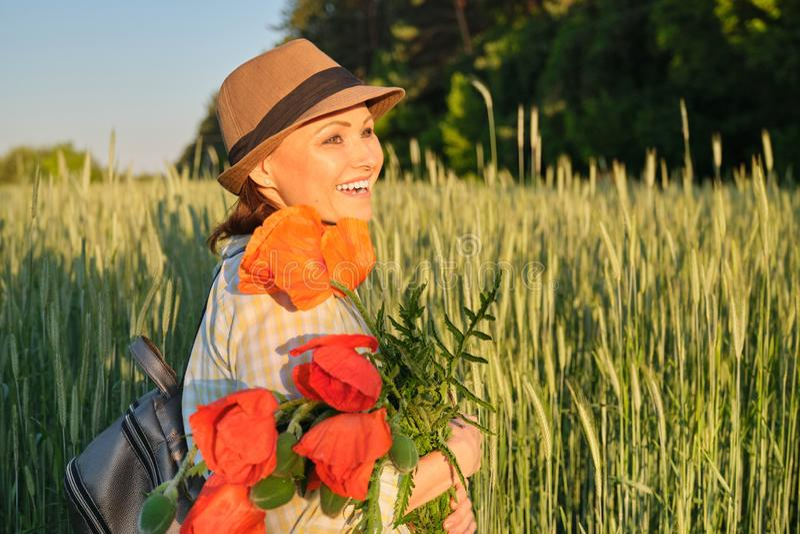 На открытом воздухе портрет счастливой зрелой женщины с букетами красных цветков маков стоковое изображение