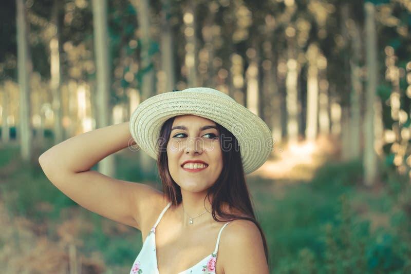 На открытом воздухе портрет усмехаясь красивой девушки брюнета нося шляпу солнца стоковая фотография