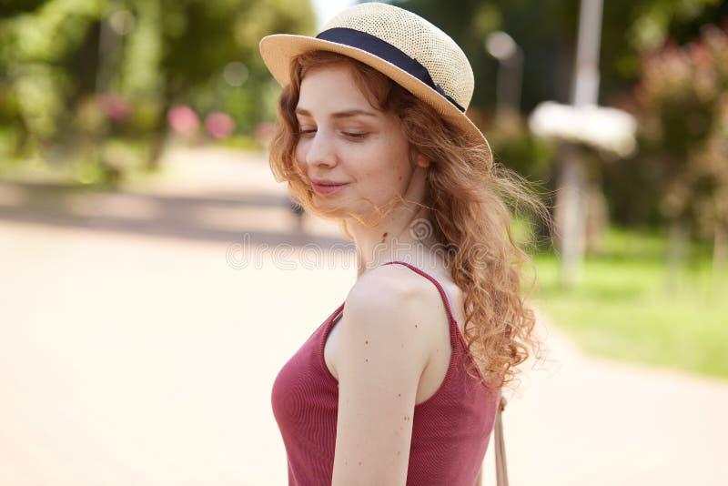 На открытом воздухе съемка внимательной привлекательной молодой дамы со справедливым вьющиеся волосы, представляющ в парке, имеющ стоковая фотография