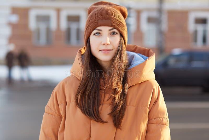 На открытом воздухе съемка женщины брюнета европейской с приятным возникновением, носит шляпу и коричневая куртка, смотрит сразу  стоковые изображения