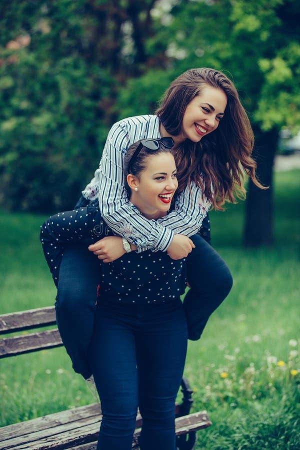 На открытом воздухе съемка молодой женщины нося ее женского друга на ей назад стоковое изображение rf