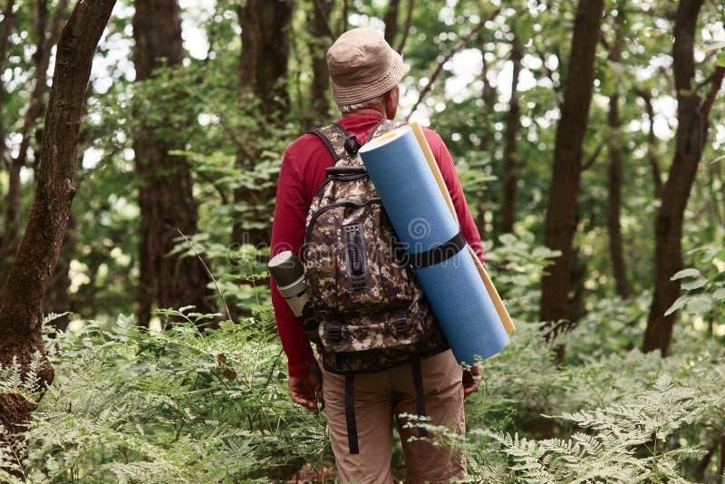 На открытом воздухе съемка перемещений человека eldery, который нужно покрыть горы, туриста старика в горах носит рюкзак и полови стоковые изображения