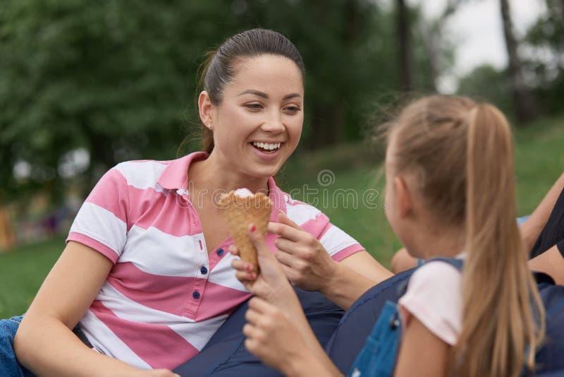 На открытом воздухе съемка счастливой матери с ее doughter сидя в парке, маленькой девочке деля с мамой ее мороженое, маму смеясь стоковое изображение