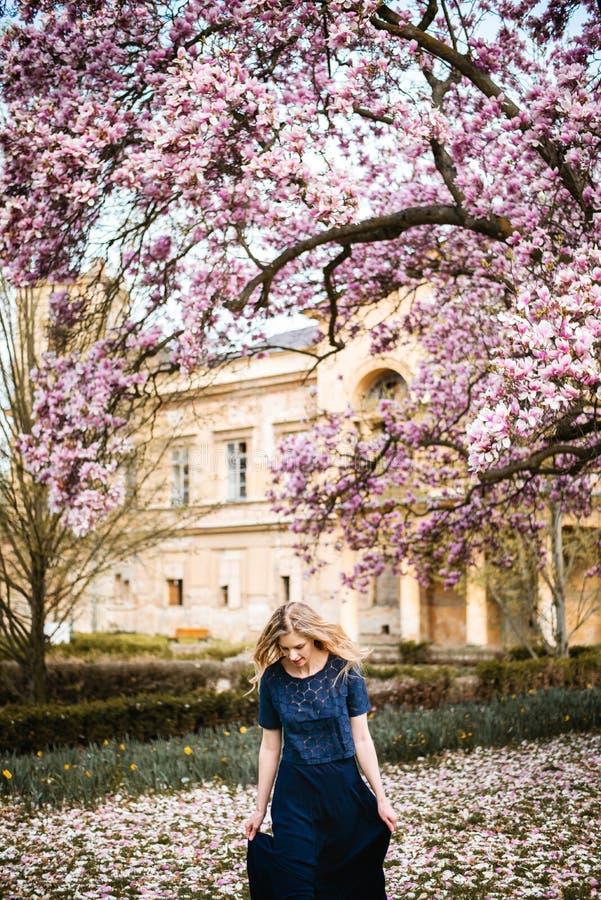 На открытом воздухе фото хода молодой женщины и потеха иметь вокруг дерева магнолии полностью зацветают стоковые изображения rf