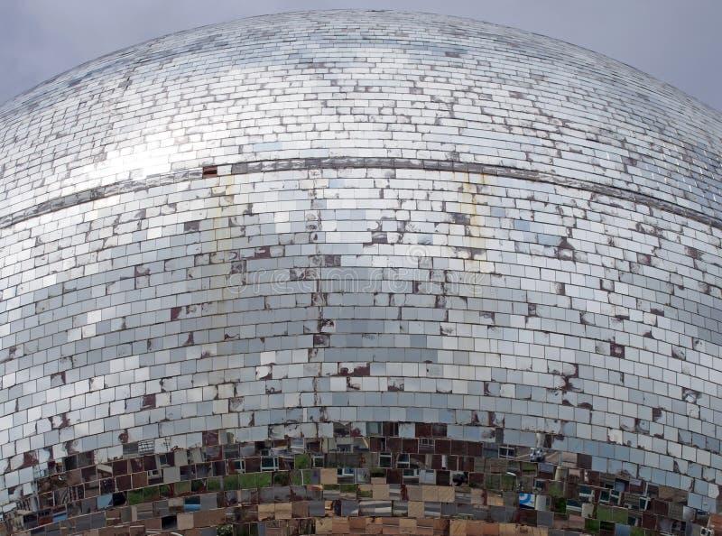 На открытом воздухе шарик зеркала сделанный тысяч частей стекла отражая серое облачное небо и разделенные изображения городской у стоковая фотография