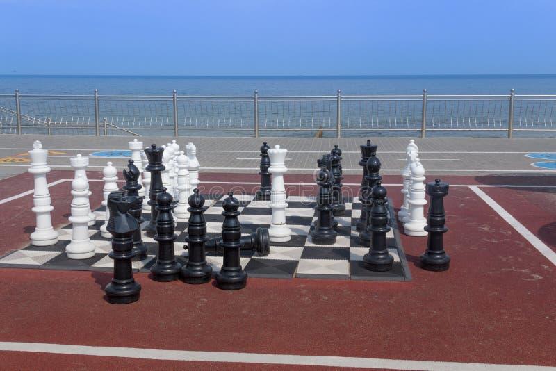 На открытом воздухе шахматы на пляже высотой моря в человеческом росте стоковое фото rf