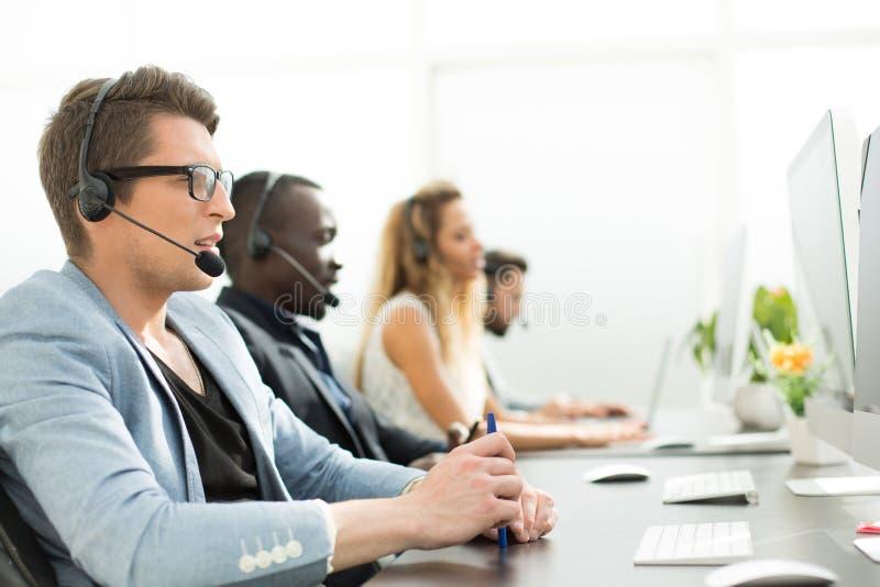 На переднем плане центр телефонного обслуживания работника в офисе стоковое изображение rf