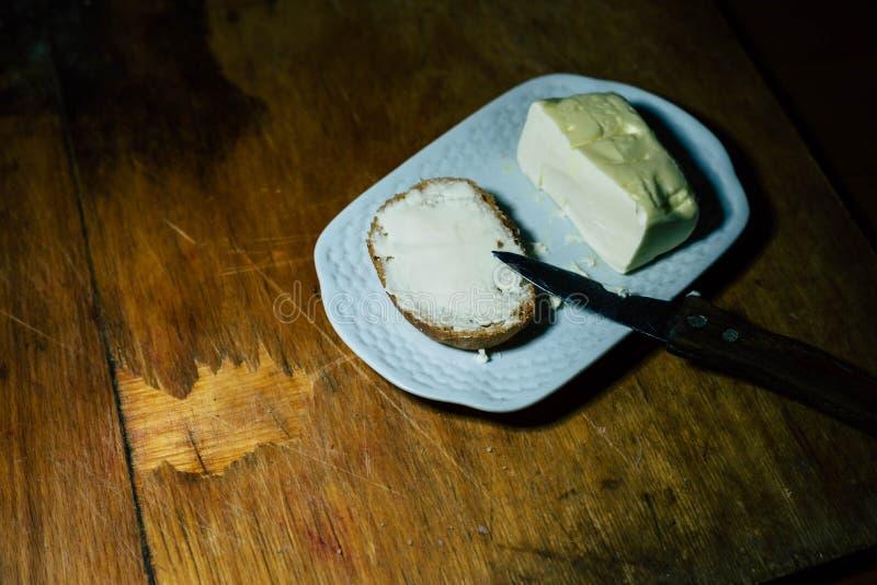 На плите, смажьте кусок хлеба с маслом стоковые фото