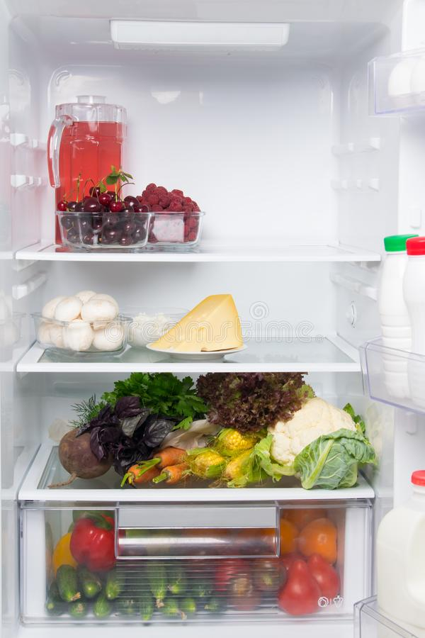 На полках белого холодильника, запас еды, свежие овощи, ягоды, сыр, грибы, творог, компот в кувшине стоковые изображения