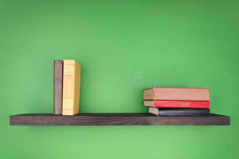 На предпосылке дзэна черная полка с текстурой дерева 3 книги от левой лож на праве 2 книги стоковая фотография