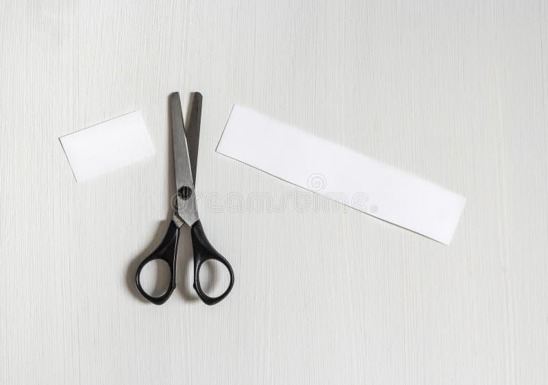 На предпосылке света ножницы отрезали надпись куска бумаги стоковые изображения