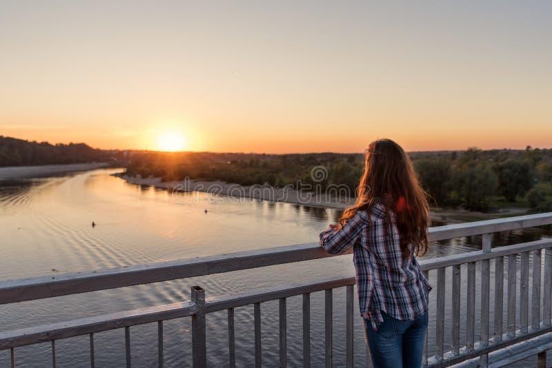 На пристани с стальными перилами над водой стоит молодая женщина девушки с ей назад с вьющиеся волосы на заходе солнца стоковые изображения