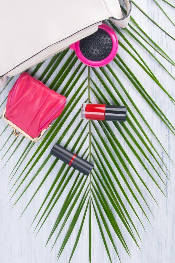 На светлой предпосылке и зеленых лист пальмы, открытой белой косметической сумки и разбросанных объектов, красного маникюра, губн стоковое изображение rf
