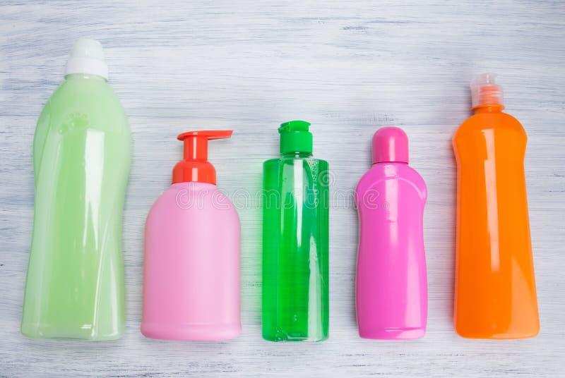 На светлой предпосылке, пестротканых бутылках с жидкостями для очищая поверхностей, моя блюд и моя одежд, аранжированных в a стоковые изображения rf