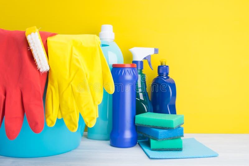 На светлом - серая и желтая предпосылка, пестротканые бутылки с жидкостями и порошок, губки, для очищая поверхностей, моя стоковые фотографии rf
