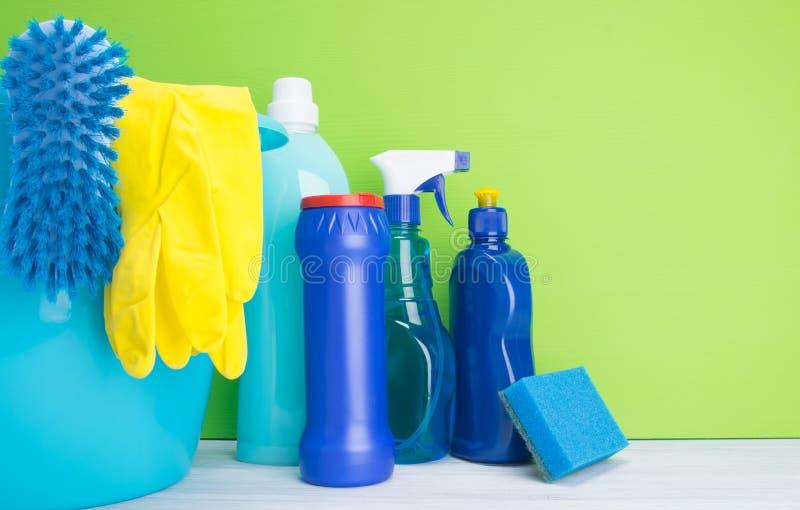 На светлом - серая и зеленая предпосылка, пестротканые бутылки с жидкостями и порошок, губка, для очищая поверхностей, моя стоковое фото