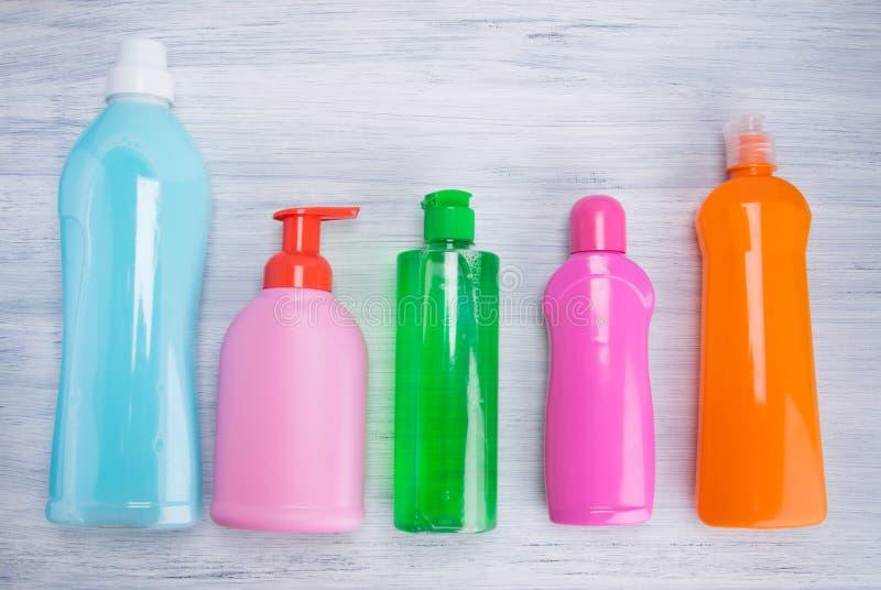 На светлом - серая предпосылка, пестротканые бутылки с жидкостями для очищая поверхностей, аранжировала в ряд стоковое фото