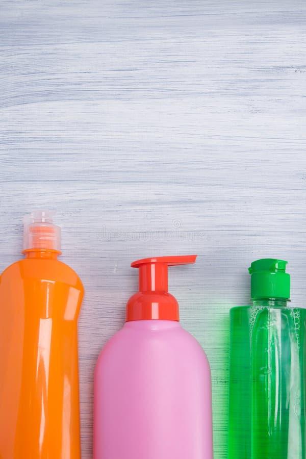 На светлом - серая предпосылка, пестротканые бутылки с жидкостями для очищая поверхностей, с местом для надписи стоковые фото