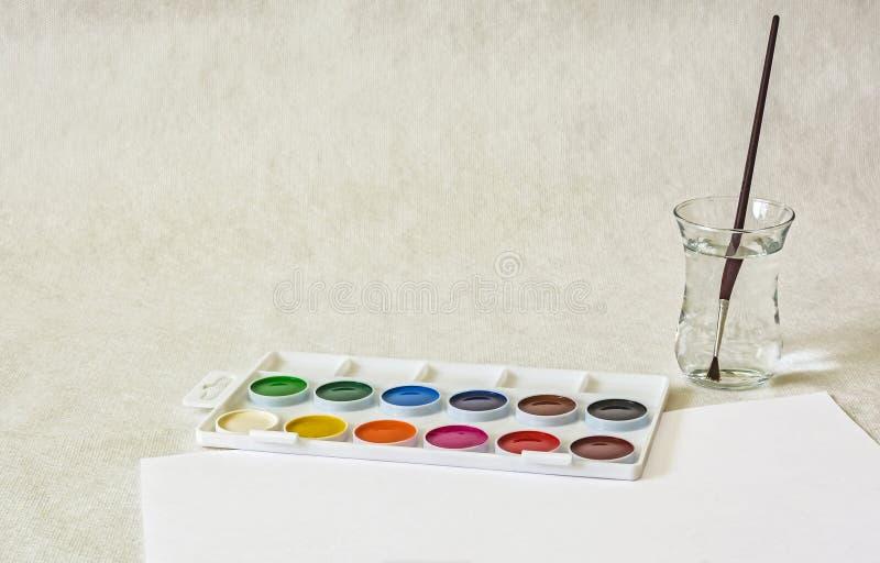На светлой поверхности комплект красок акварели и там стоковое изображение rf